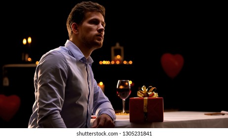 Upset man sitting in restaurant with red gift box, girlfriend missing date