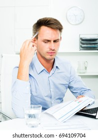 Upset  man sitting at working desk with laptop and having work troubles in office