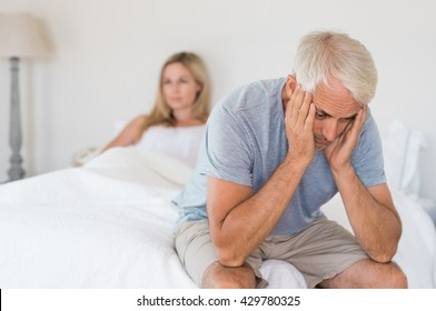 Upset mature couple ignoring each other. Close up of a worried senior man in tension at bed. Senior couple angry with each other after a fight.