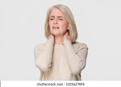 Upset mature old woman massage hurt stiff neck feel fibromyalgia osteoarthritis pinched nerve, tired sad mid aged senior lady rubbing muscles to relieve pain isolated on white grey studio background