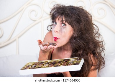 Upset mature woman feels a little bit better after eating chocolates in her bedroom
