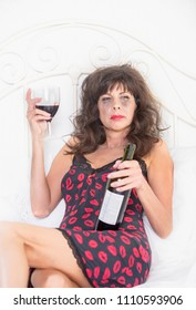 Upset mature woman in nightie drinking wine in her bedroom