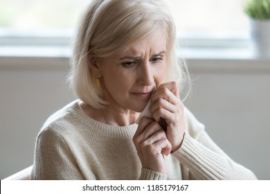 Upset middle aged woman wiping tears crying feeling depressed hopeless lonely after divorce, desperate old senior widow thinking of disease, sorrow or grief, mature elderly lady mourning concept