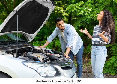 Upset middle-eastern couple having broken car while countryside trip, puzzled arab guy checking engine, emotional brunette lady looking up, sad mixed race family stuck in the middle of road
