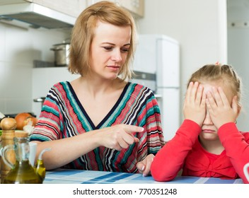 Upset mother shaming little daughter for misbehaviour in domestic interior