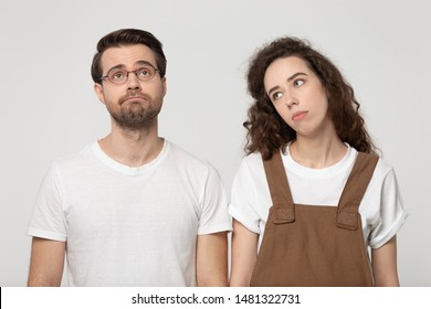 Upset not concentrated exhausted millennial couple feeling bored, lack of motivation or interest, looking away, isolated on grey white studio background. Sad young friends need weekend rest.