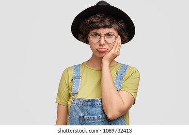 Upset offended female student feels frustration, being in depression as fails exam, wears hat and denim overalls, isolated on white background. Lovely unhappy woman purses up lips in dissatisfaction