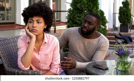 Upset offended girl ignoring boyfriend, turned away, misunderstanding, conflict