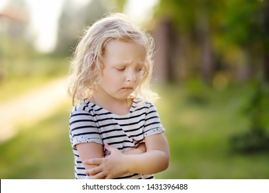 Upset or offended little girl standing on street of small town's or village's. ?risis of three years. Escape from the house.