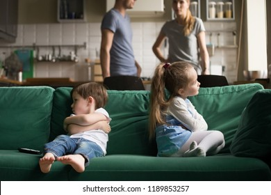 Upset offended toddler brother and sister sitting separately on couch, sofa with arms crossed, little girl and boy ignoring each other, not talking, puzzled parents discuss situation