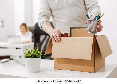 Upset office manager packing the box and leaving the office