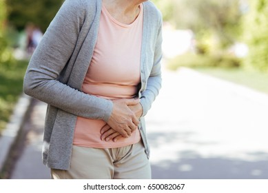 Upset old woman having sudden pain in the stomach outdoors