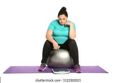 Upset overweight woman with scale, measuring tape and fitness ball on white background
