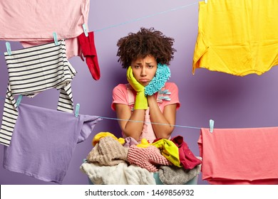 Upset overworked housewife hangs clothes on washing line with clothespins, busy doing housework, wears casual outfit and rubber protective gloves, surrounded with laundry. Washing day concept