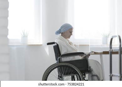 Upset patient sick with tumor sitting in a wheelchair while browsing tablet