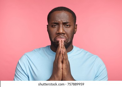 Upset praying sorrorful African male asks for forgiveness, feels guilty, curves lower lip, hopes for apology or excuse, isolated over pink background. Young dark skinned male prayer poses indoor