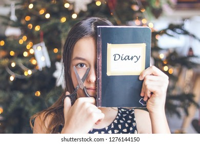 Upset preteen girl holding scissors and black diary journal in front of her face intenting to destroy and wreck it. Teenager psychology and dissapointment. Secrecy of private life.