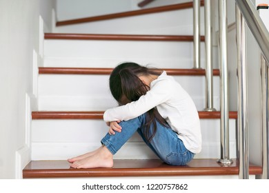 Upset problem child with head in hands sitting on staircase concept