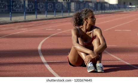 Upset with results biracial sportswoman lonely sitting in middle of track