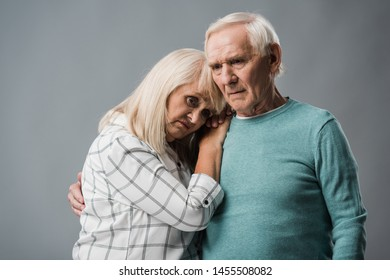 upset retired man hugging frustrated wife isolated on grey