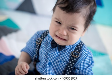 Upset, sad cute 11 month old mixed race Asian Caucasian boy dressed in braces and bow tie on a colourful geometrically shaped bed cover
