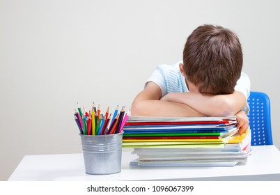 Upset schoolboy with pile of school books and notebooks