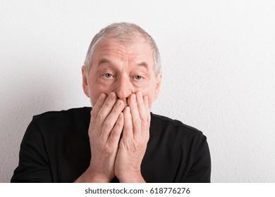 Upset senior man with headache, holding his mouth, studio shot.
