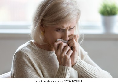 Upset senior woman crying at home feeling lonely and unneeded, sad aged female wipe tears sorrow or grieve for passed husband, disappointed elderly lady in despair having problems or life difficulties