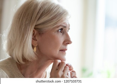 Upset senior woman looking in distance remembering old times, sad aged female sit at home feeling lonely missing passed husband, elderly lady crying near window having difficult life situation