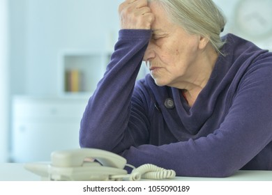 upset senior woman with  phone