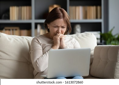 Upset senior woman sit on sofa in living room feel stressed crying reading bad unpleasant news on laptop, sad distressed middle-aged female worry get negative notice or email online on computer