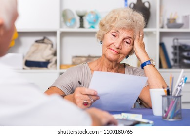 Upset senior woman sitting at home table discussing with husband their bills