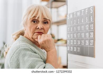 upset senior woman touching head and looking at camera
