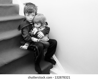 Upset siblings sitting on the stairs.