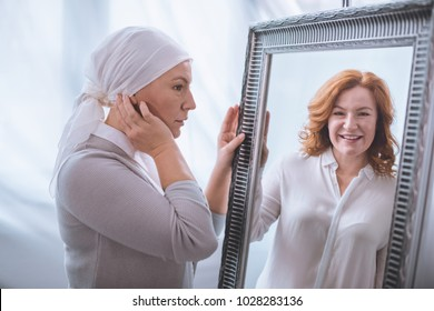upset sick mature woman in kerchief looking at smiling reflection in mirror, cancer concept