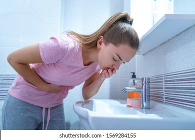 Upset sick woman suffers from nausea and vomiting due to digestive and belly illness problems at home. Morning toxicosis at first trimester of pregnancy. Stomach infection due to food poisoning