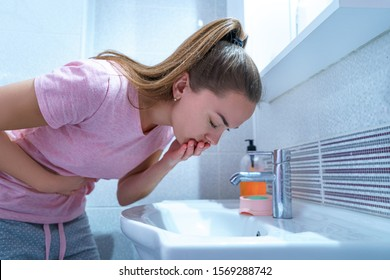 Upset sick woman suffers from nausea and vomiting due to digestive and belly illness problems at home. Toxicosis at first trimester of pregnancy. Stomach infection due to food poisoning
