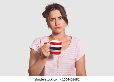 Upset sleepy lovely young woman holds cup of coffee, drink refreshing beverage to feel brave early in morning, dressed in casual clohes, has displeased expression, isolated over white background.