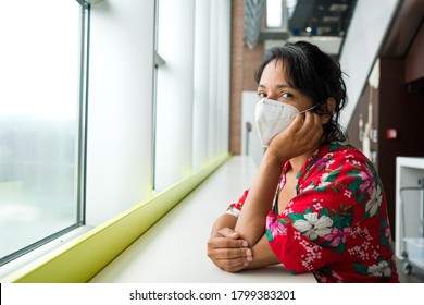 upset spanish young woman at airport wearing surgical face mask,traveling during the covid-19 pandemic. Corona virus has caused a crisis in the travel and aviation industry