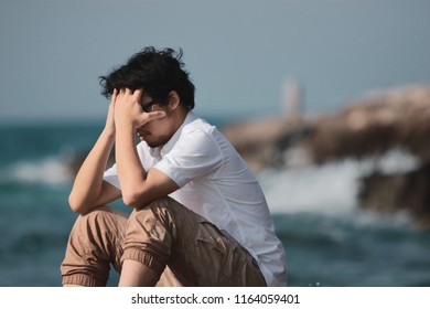 Upset stressed Asian man bend down head at sea shore.