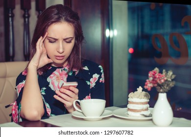 Upset stressed unhappy woman holding cellphone disgusted with message she received isolated coffee shop background. Sad looking human face expression emotion feeling reaction perception body language