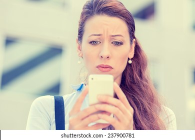 Upset stressed woman holding cellphone disgusted with message she received isolated corporate building background. Sad looking human face expression emotion feeling reaction perception body language