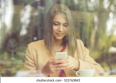 Upset stressed woman holding cellphone disgusted with message she received isolated coffee shop background. Sad looking human face expression emotion feeling reaction perception body language