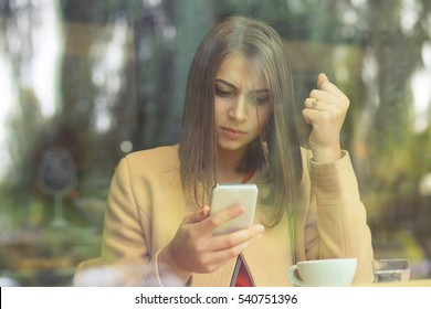 Upset stressed woman holding cellphone angry with message she received fist up on phone isolated coffee shop background. Sad looking human face expression emotion feeling body language