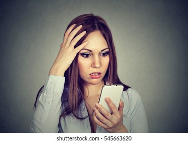 Upset stressed woman looking at cellphone worried with message she received isolated on gray background. Human face expression emotion feeling reaction perception