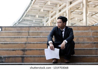 Upset stressed young Asian business man sitting on stairs and suffering from severe depression. Unemployment and layoff concept.