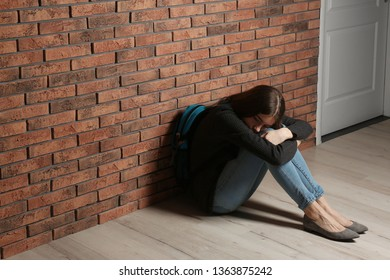 Upset teenage girl with backpack sitting on floor near wall. Space for text