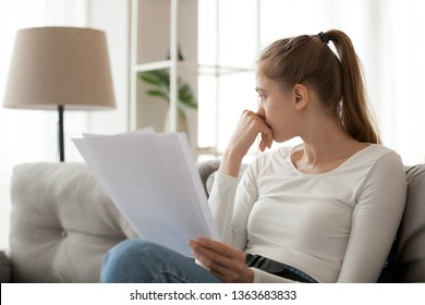 Upset thoughtful woman holding paper document in hands, sitting on sofa, looking in distance, thinking about received bad news, notification, checking bills, bankruptcy, having problem
