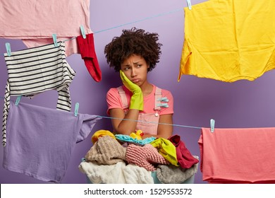 Upset tired Afro woman busy with housework, wears rubber gloves, dries clothes, has much jobs around house, stands near basket of dirty linen, isolated over purple background. Laundry day concept