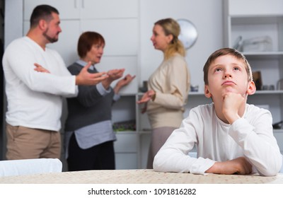Upset tired son suffering from parental arguing at home
